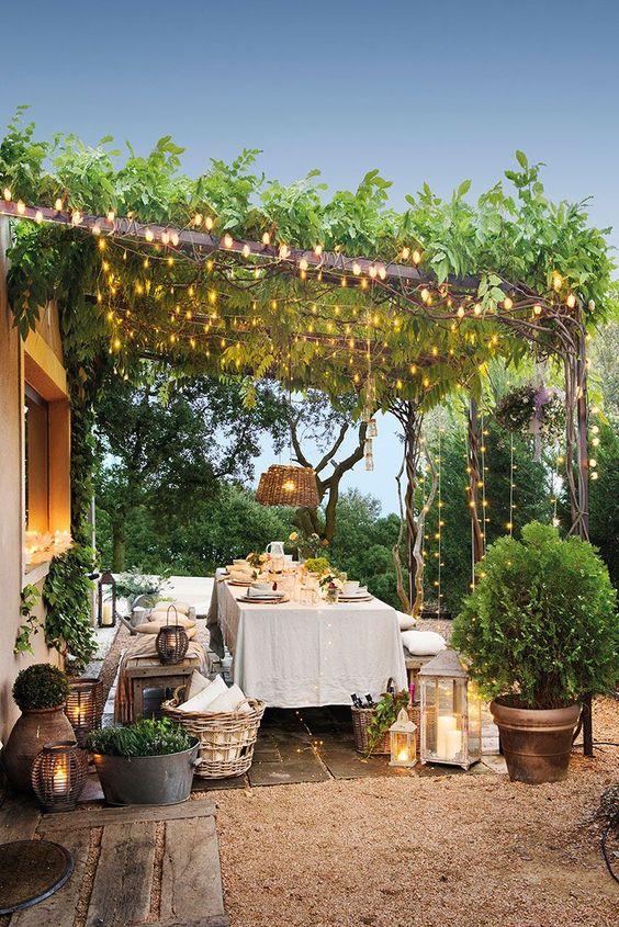 una zona pranzo all'aperto con mobili in legno, cesti, piante in vaso, lanterne a candela e luci creano un baldacchino sullo spazio