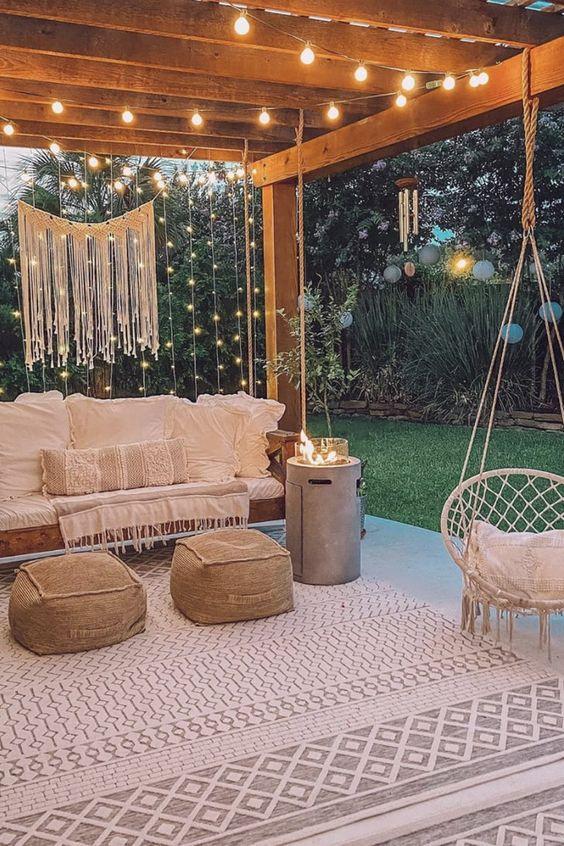 un accogliente patio nel terrazza con mobili boho, tessuti neutri, luci stringa e macramè sullo spazio