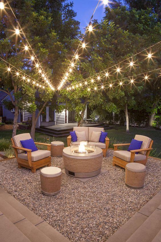 un elegante soggiorno all'aperto moderno con un pozzo del fuoco moderno e luci stringa sullo spazio è accogliente e chic