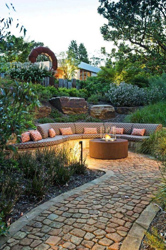 un accogliente giardino con una panchina incorporata, un pozzo del fuoco contemporaneo e lampade da esterno per un look elegante e alla moda