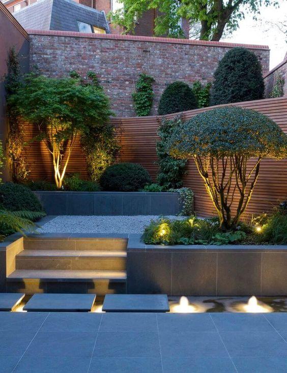 un elegante cortile minimalista con luci incorporate e alberi illuminati che vengono evidenziati con queste luci