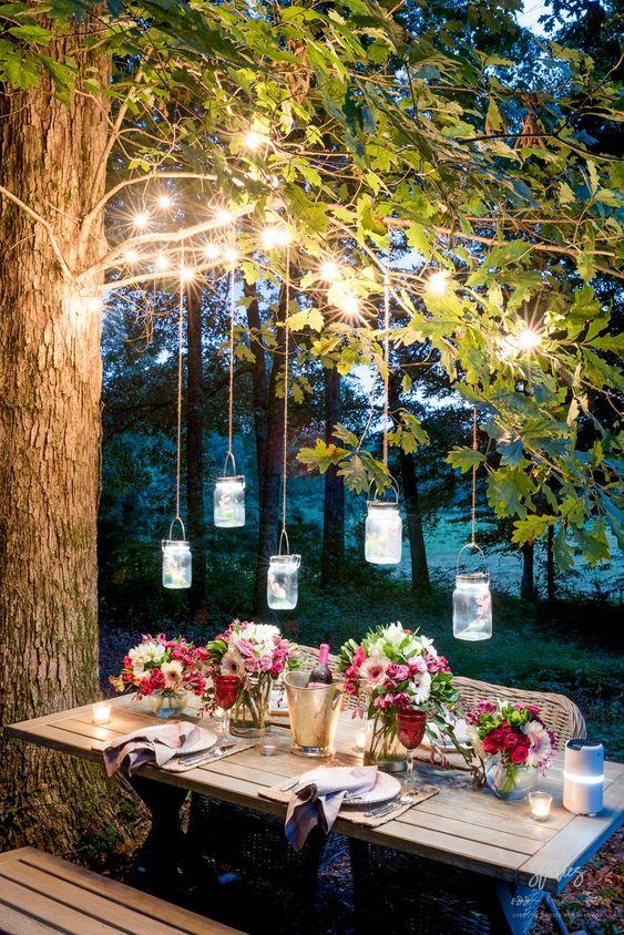 le luci delle corde sui rami e le lanterne dei vasi pendenti sopra il tavolo più le candele sul tavolo sono molto accoglienti