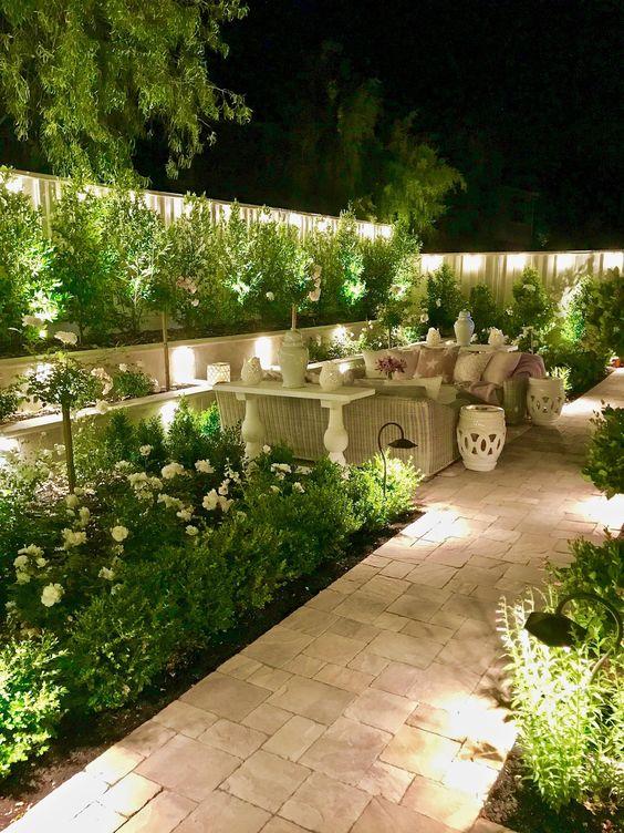 un cortile illuminato con lampade da giardino da esterno tutt'intorno, nascoste e non, è uno spazio giardino molto accogliente
