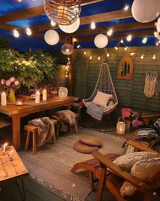 un terrazza boho rilassato e accogliente con luci di carta e corde, con candele e lanterne a candela
