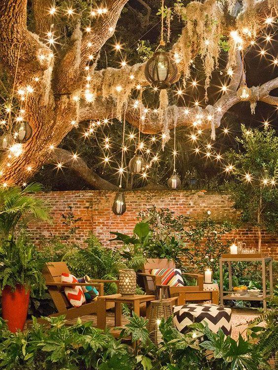 uno spazio nel cortile con molte luci a corda, lampade a sospensione in rattan e lanterne a candela in tutto lo spazio è molto bello