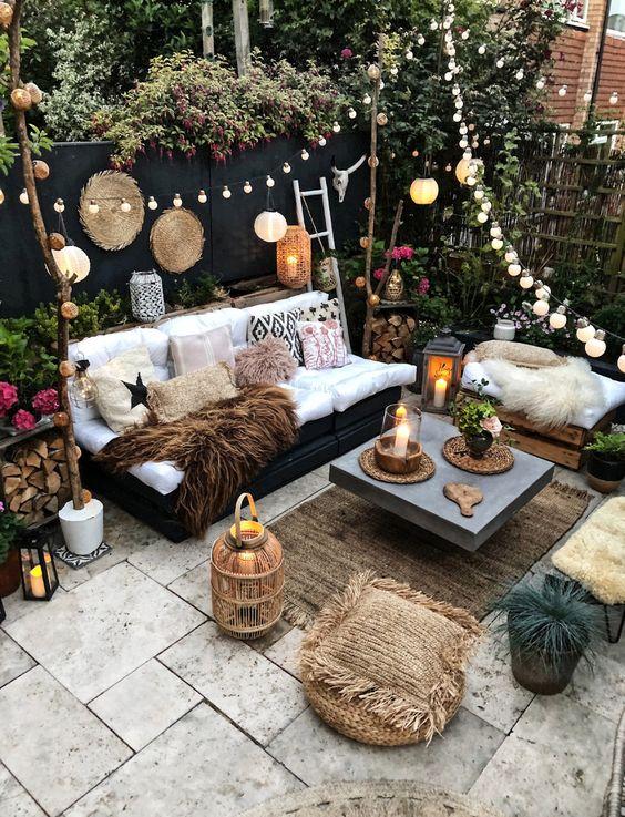 un giardino boho con lanterne a candela, luci a corda e lampade di carta nello spazio, fiori in vaso e vegetazione intorno