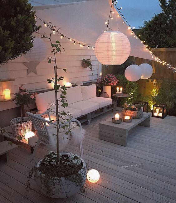 un ponte accogliente con pallet moderni e mobili in rattan, lanterne a candela, luci a corda e lampade di carta nello spazio