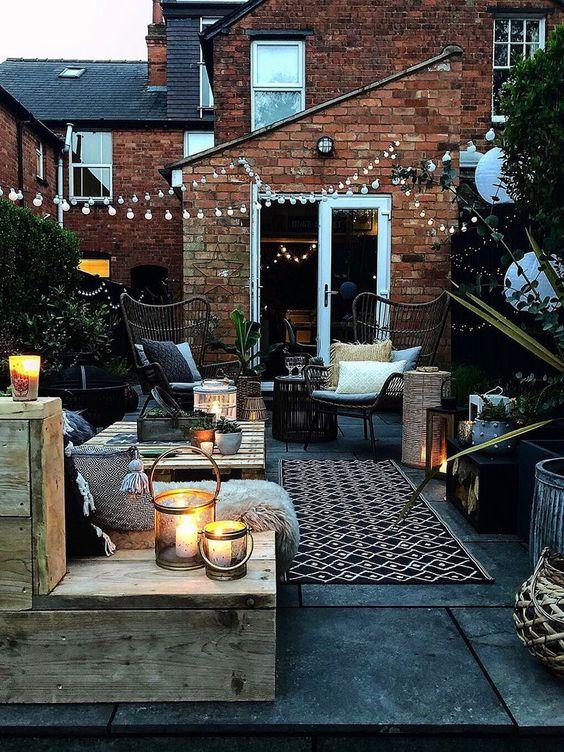 un accogliente cortile con pallet e mobili in rattan, con tessuti stampati, lanterne a candela e luci a corda sullo spazio