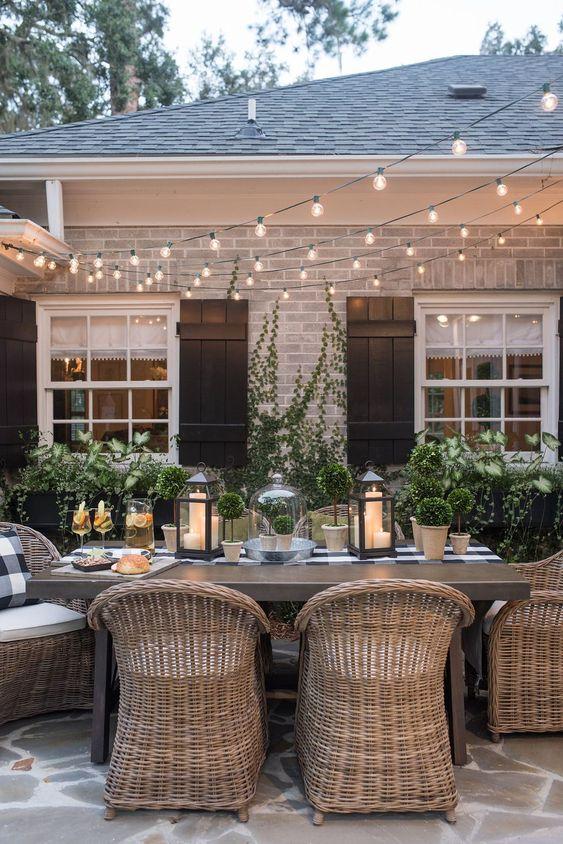 un elegante spazio da pranzo nel cortile con un tavolo in legno e sedie in rattan e luci a corda sullo spazio