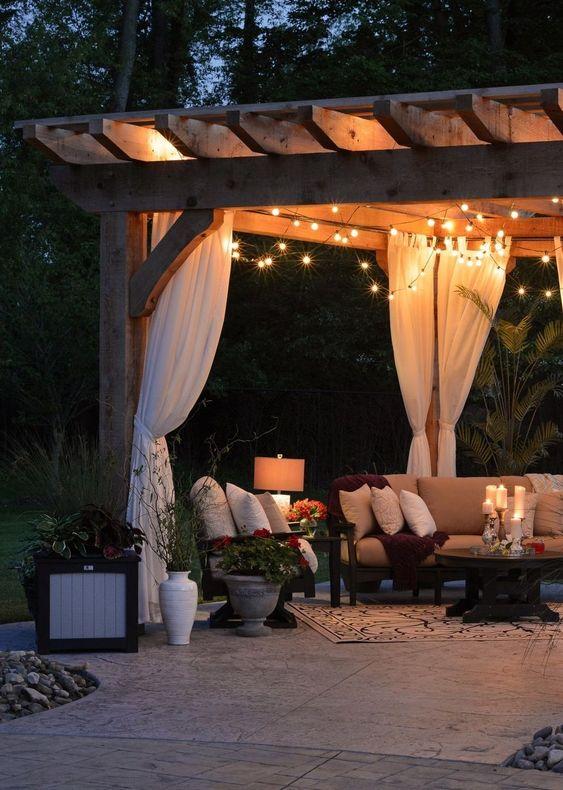 luci a filo, lampade da terra e candele sul tavolo rendono questo soggiorno all'aperto molto accogliente e molto chic