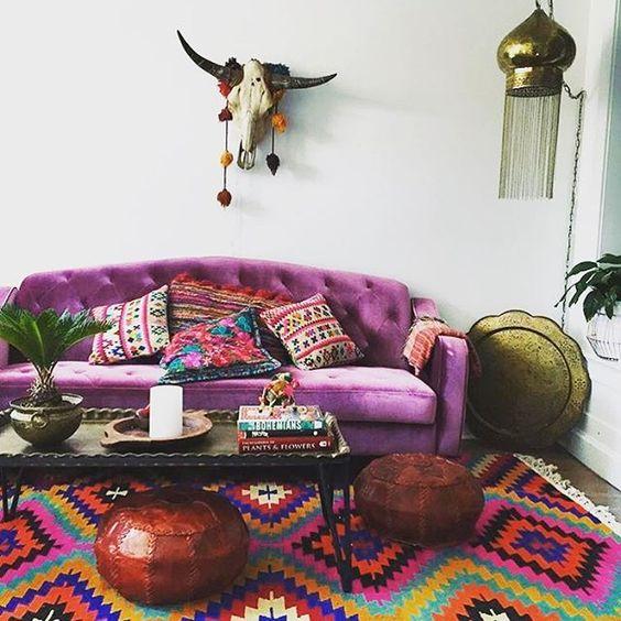 un colorato soggiorno boho con un divano viola, un tappeto colorato, pouf bown, un tavolo basso, un teschio e una lampada a sospensione