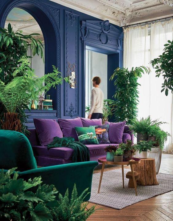 un soggiorno luminoso con pareti blu audaci, un divano viola, una sedia color smeraldo, piante in vaso e un grande specchio