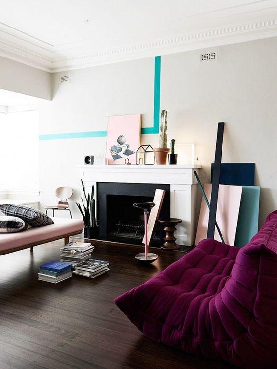 un soggiorno contemporaneo con un caminetto non funzionante, un divano arrossato e un divano viola scuro, blocchi di colore e libri