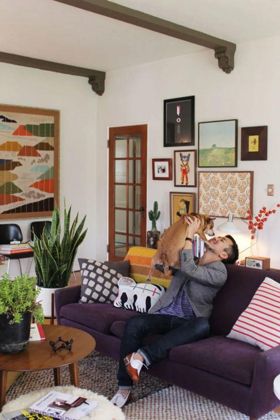 un soggiorno colorato con un divano viola intenso, una galleria a muro luminosa, sedie nere e tavolini non corrispondenti più travi in legno