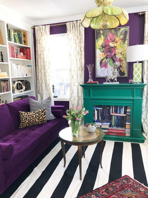 un soggiorno colorato con un muro di accento viola scuro e un divano coordinato, un tappeto a righe, una lampada a sospensione floreale e un camino color smeraldo con libri