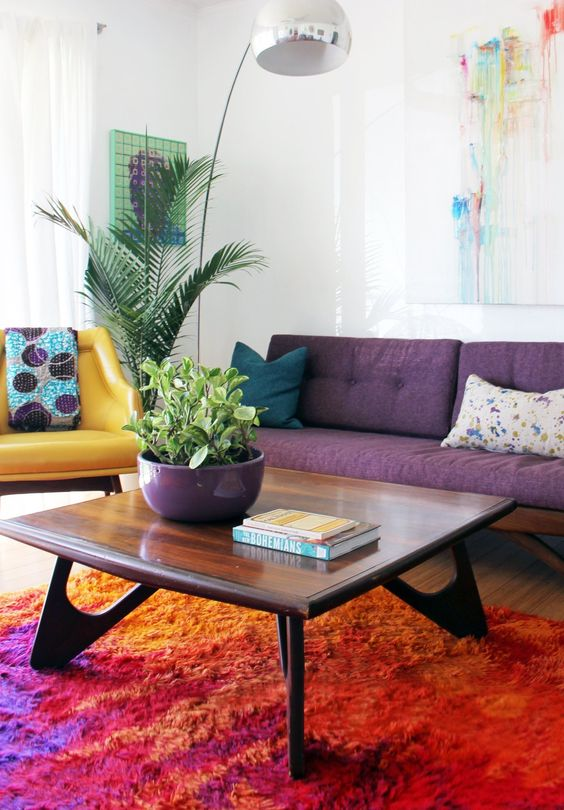 un soggiorno colorato con un divano viola, una sedia gialla, un tavolino da caffè macchiato chic e opere d'arte luminose e una lampada da terra