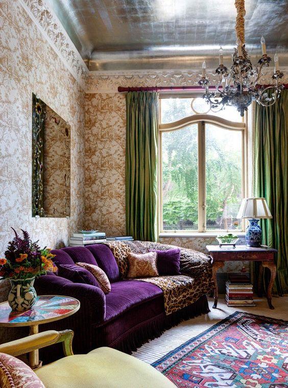 un sofisticato soggiorno vintage con carta da parati stampata, un divano viola, un delizioso lampadario, curtais verdi e un tappeto stampato