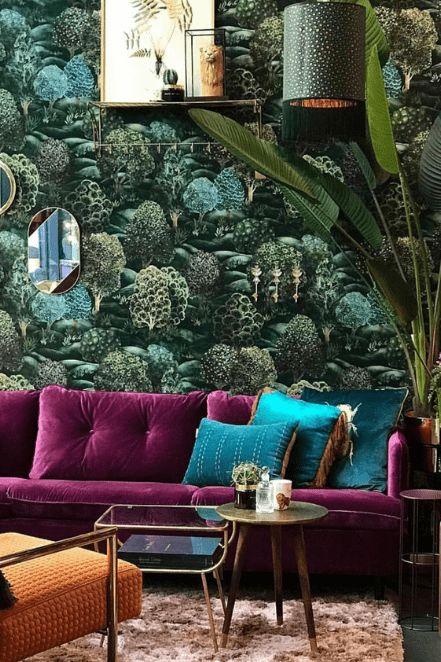 un soggiorno massimalista con un muro di accento botanico, un divano viola, cuscini verdi, una lampada a sospensione e una pianta in vaso più tavoli non corrispondenti