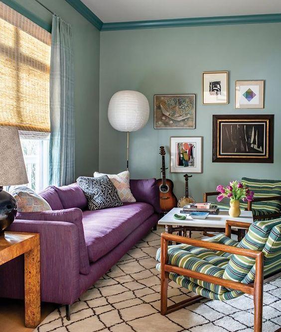 un bel soggiorno con pareti verde chiaro, un divano viola, sedie a righe, una graziosa galleria a muro e un tavolino da caffè chic