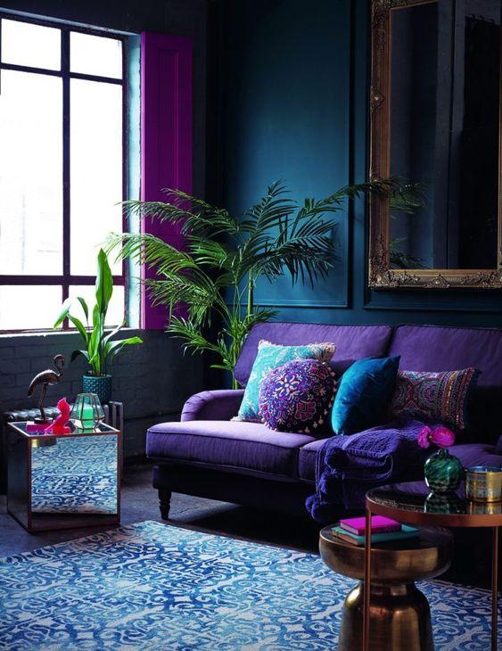 un soggiorno lunatico con pareti rivestite di pannelli blu scuro, un divano viola, tavoli metallici e uno specchio, un tappeto blu e tende rosa acceso
