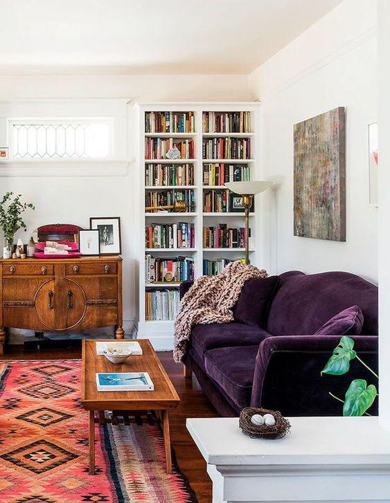 un moderno soggiorno della metà del secolo realizzato in colori neutri e pieno di colore: un tappeto stampato, un divano viola scuro, mobili colorati e una libreria incorporata