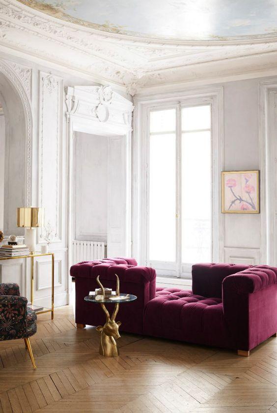 uno squisito soggiorno neutro con un divano viola di velluto, una console in vetro e oro, una sedia stravagante e un bel tavolo di corna