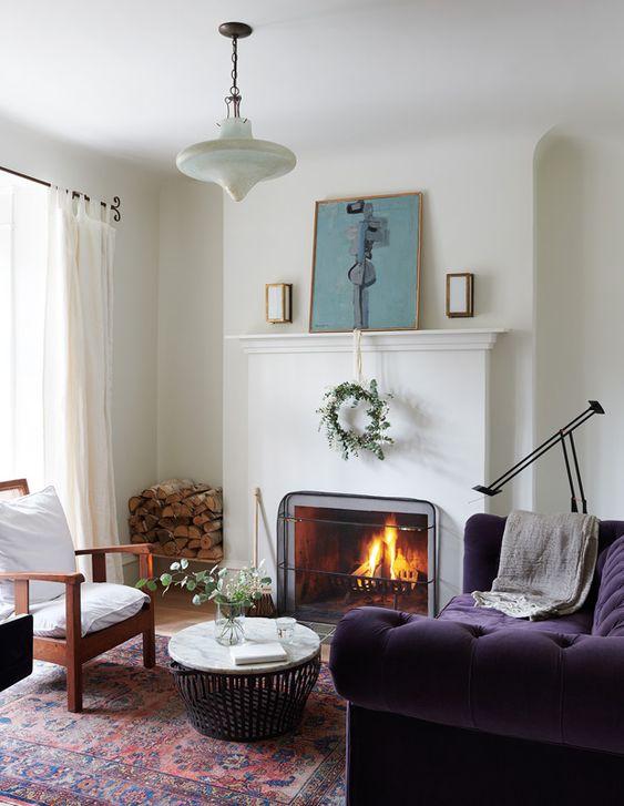 un bellissimo soggiorno neutro con un camino, una mensola del camino con decorazioni, una sedia bianca e uno splendido divano viola scuro e un tavolo rotondo