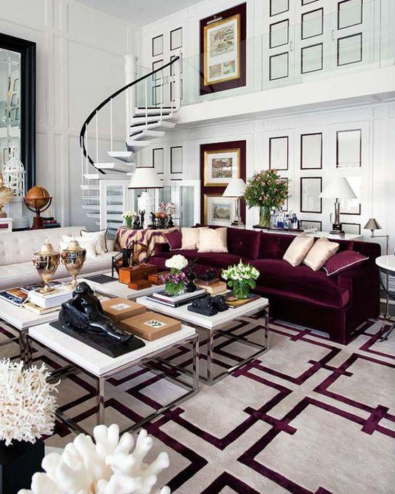 un bel soggiorno con pareti rivestite di pannelli bianchi, un divano color crema e viola, un gruppo di tavolini da caffè e un tappeto bianco e viola stampato