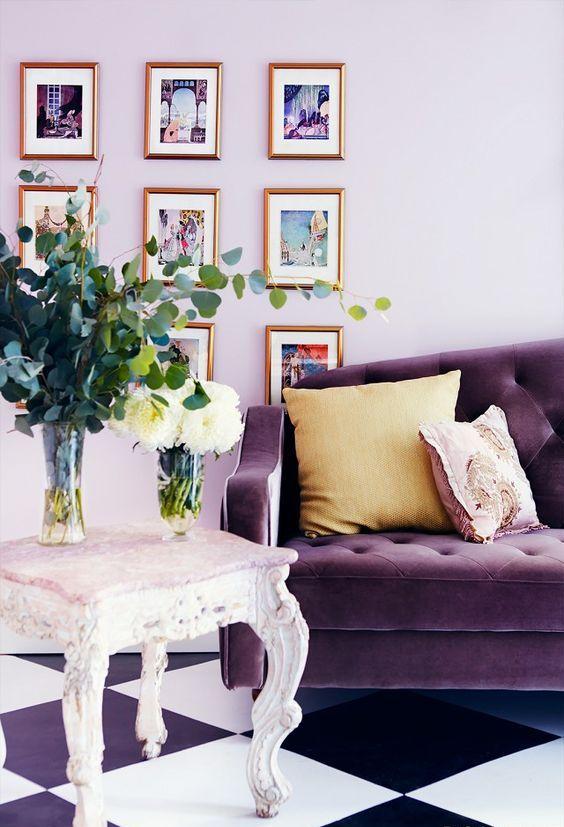 un soggiorno chic con pareti lilla, un divano viola, un raffinato sgabello intagliato e una deliziosa galleria a muro è wow
