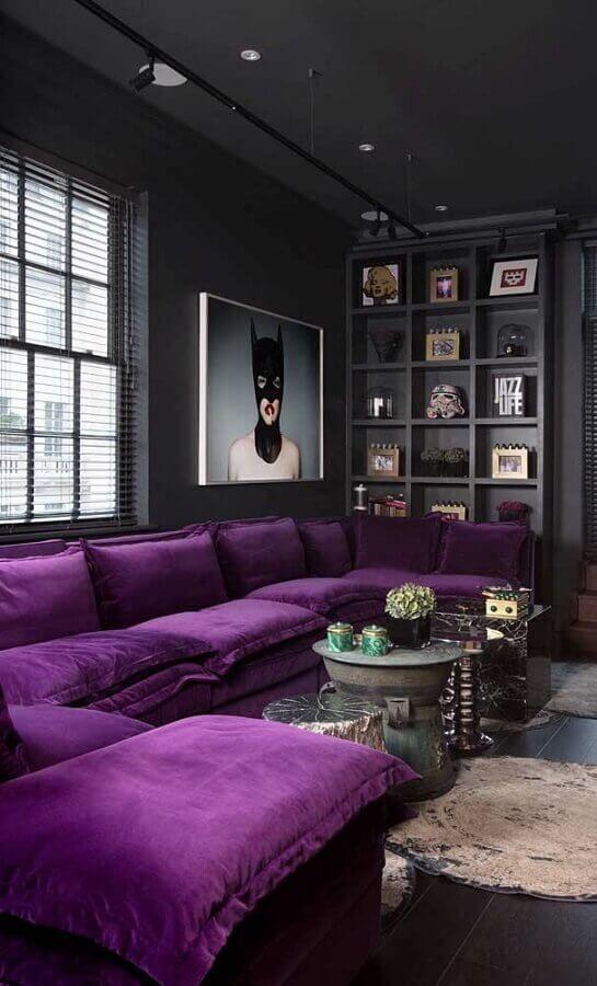 un lunatico soggiorno contemporaneo realizzato in nero e grigio grafite, uno scaffale integrato per la visualizzazione, un componibile viola e un'opera d'arte