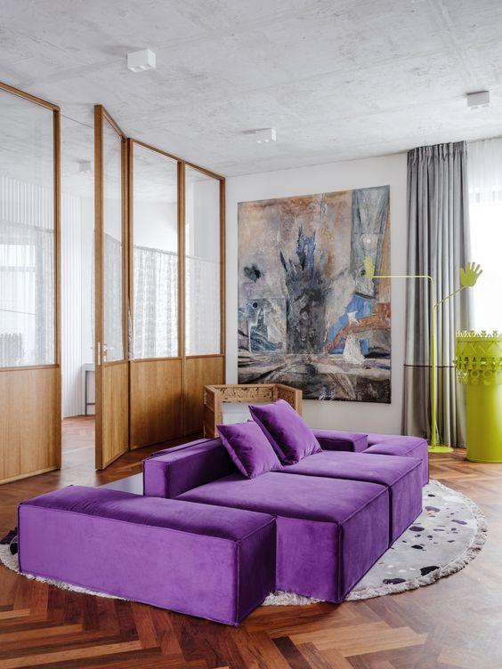 un soggiorno contemporaneo con una base neutra, un divano viola audace, un'opera d'arte, tende grigie e un tavolo giallo neon