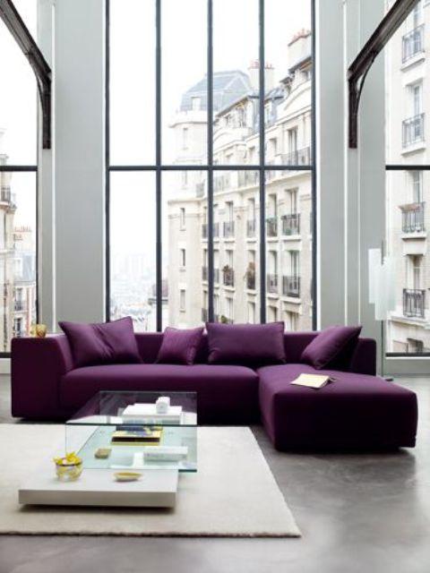 un soggiorno contemporaneo realizzato in neutri, con finestre a doppia altezza, un componibile viola, un tavolo in vetro e un tappeto neutro
