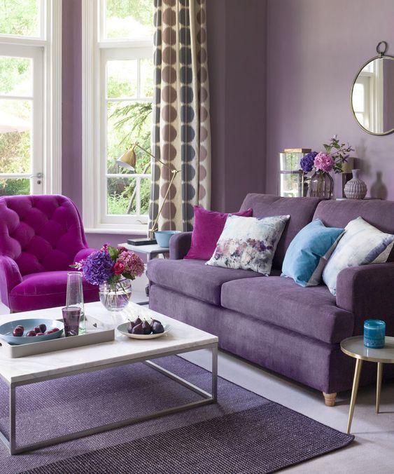 un soggiorno monocromatico con pareti color lavanda, un divano viola, una sedia rosa acceso, cuscini floreali e tende stampate