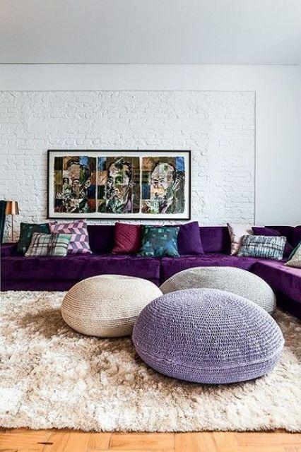 un bel soggiorno realizzato in colori neutri, con un grande componibile viola, un'opera d'arte audace, cuscini colorati e un trio di pouf