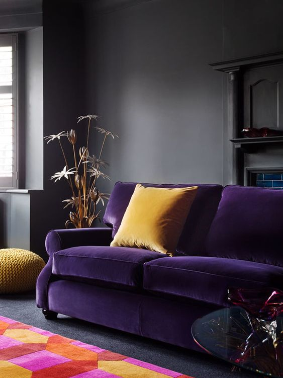 un soggiorno lunatico in grigio scuro decorato con un divano viola intenso, cuscini gialli e un tappeto geometrico colorato