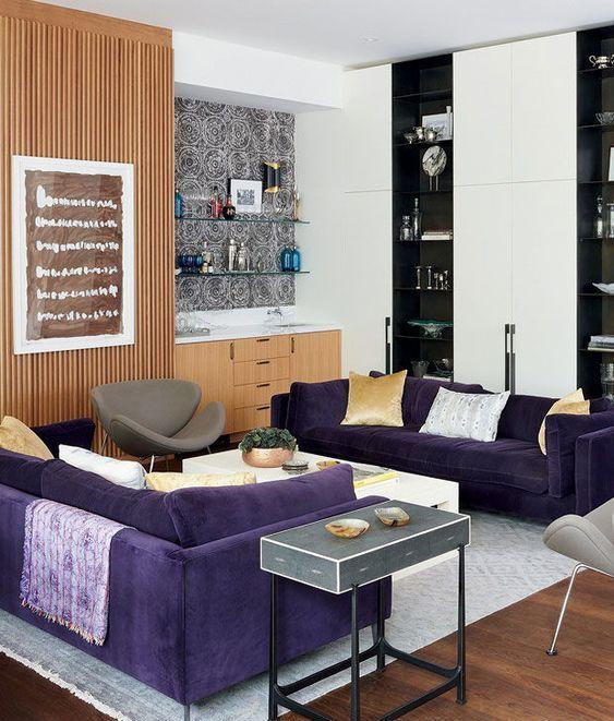 un soggiorno contemporaneo con due divani viola, sedie grigie, mobili di stoccaggio macchiati di luce e bianchi e neri