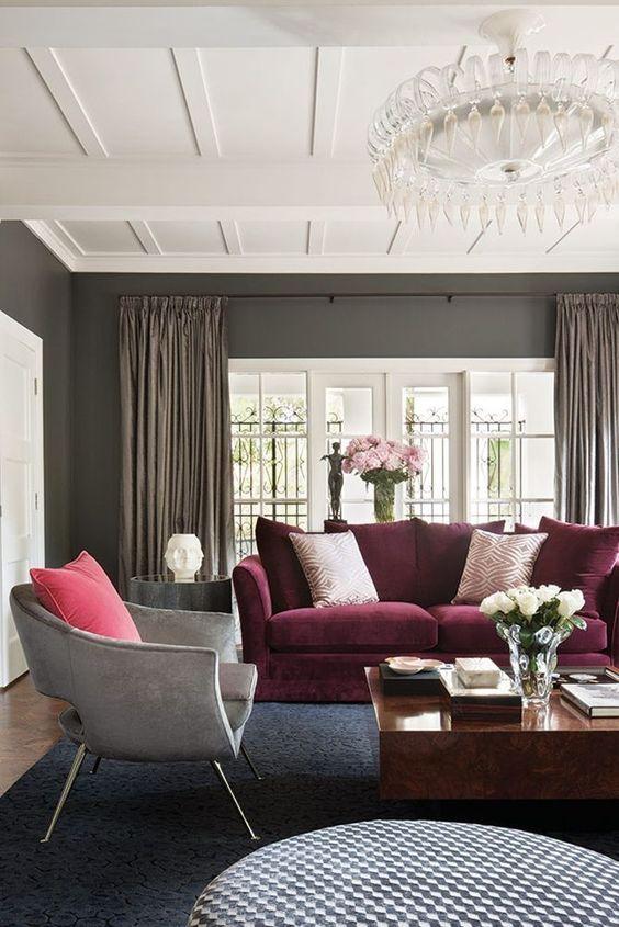 un raffinato soggiorno con pareti grigie, un divano viola, una sedia grigia, tavolini rotondi e quadrati e un accattivante lampadario di cristallo