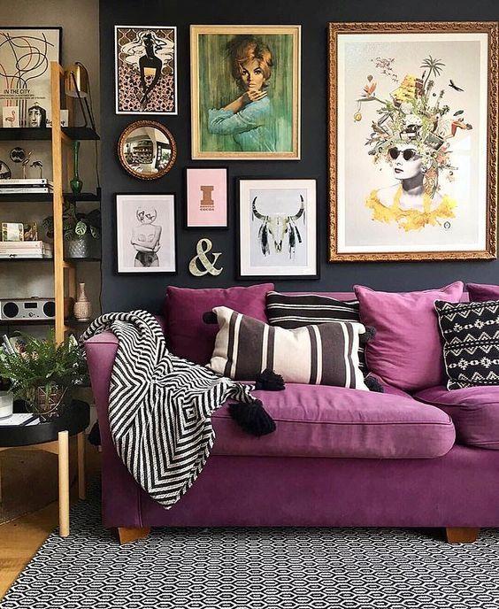 un soggiorno lunatico con un divano viola, uno scaffale aperto e una luminosa galleria a parete più cuscini stampati è bello