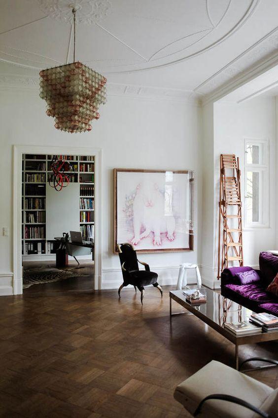 un soggiorno neutro e raffinato con mobili neri e neutri, con un audace divano viola per un tocco di colore e un lampadario accattivante