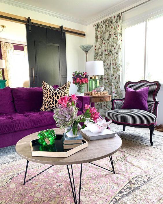 un raffinato soggiorno moderno con una porta scorrevole del fienile, un audace divano viola, una sedia raffinata, un tavolo rotondo e tende floreali