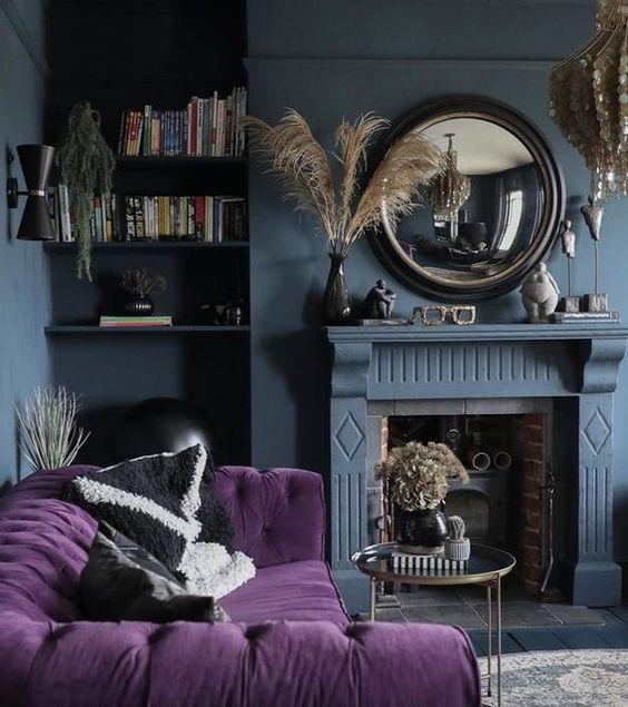 un soggiorno lunatico con pareti grigio ardesia, un camino, un divano trapuntato viola, uno specchio rotondo e un lampadario in madreperla