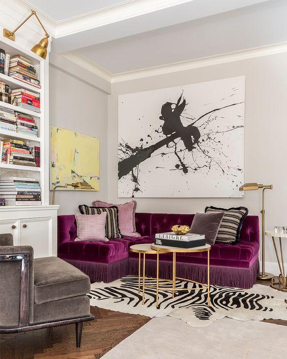 un soggiorno raffinato e audace con un componibile viola come centrotavola, un'opera d'arte grafica, una libreria integrata e tappeti a strati