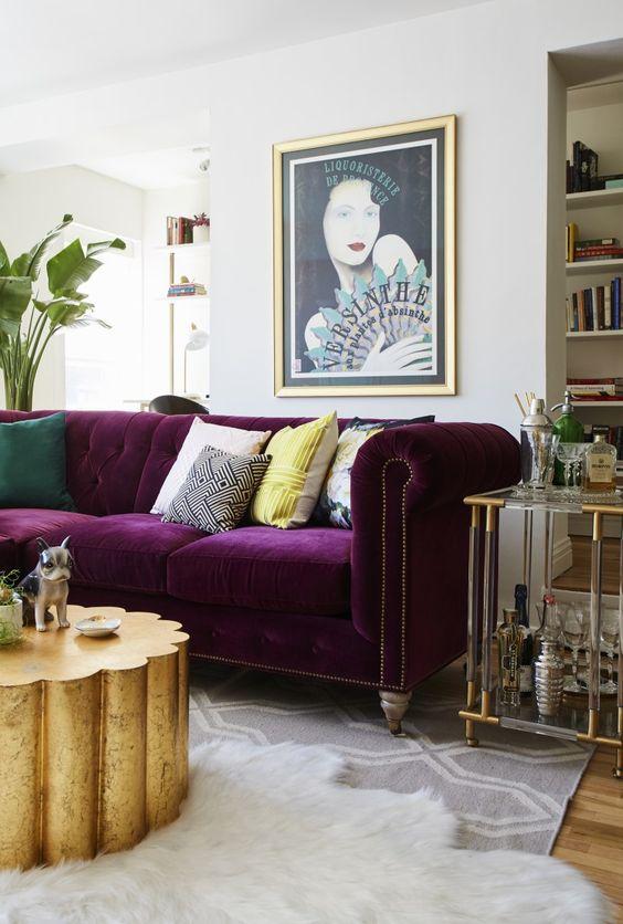 un soggiorno raffinato e glam in neutri con una libreria incorporata, un divano viola, un tavolo dorato e un bar in acrilico