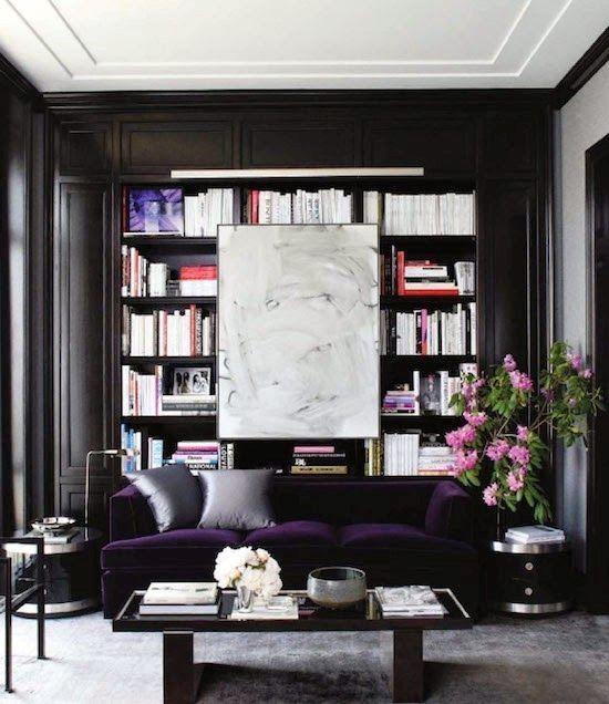 un raffinato soggiorno monocromatico moderno con librerie incorporate, un divano in velluto viola intenso per una dichiarazione di colore e un tavolo chic