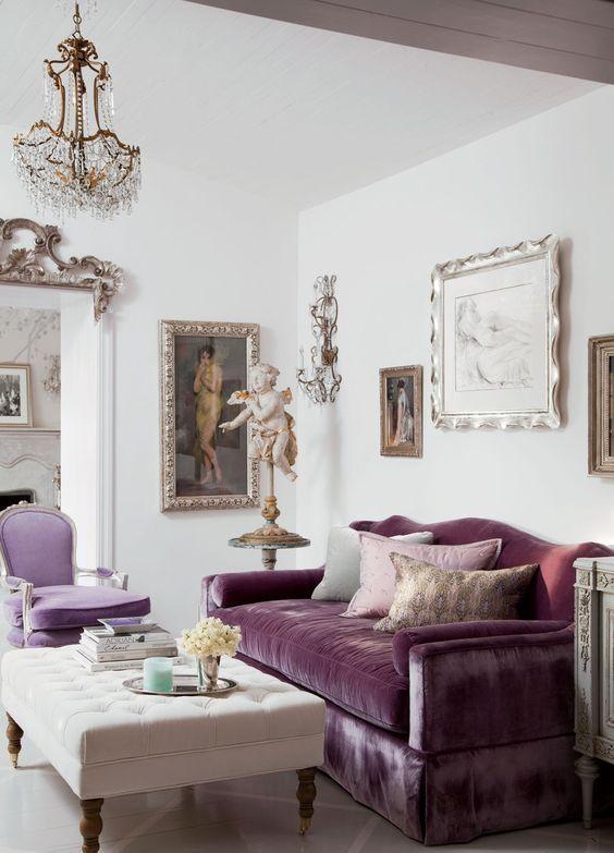 un sofisticato soggiorno neutro con un divano viola e una sedia lilla, un ottomano trapuntato color crema e una parete della galleria molto squisita