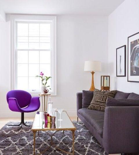 un elegante soggiorno in colori neutri, con un tappeto stampato grigio, un divano viola intenso, una sedia viola audace, una galleria a parete chic e un tavolo a specchio