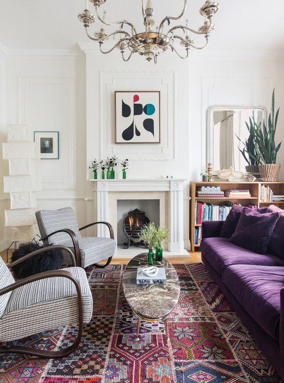 un soggiorno eclettico con un camino non funzionante, un divano viola scuro, sedie stampate, un raffinato lampadario e un audace tappeto stampato
