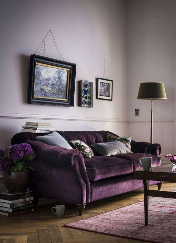 un accogliente soggiorno con pareti lilla, un raffinato divano in velluto viola, un tappeto lilla, una galleria a muro vintage, una lampada da terra verde e un tavolo macchiato di scuro