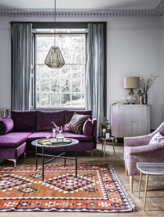 un soggiorno sereno con pareti grigio chiaro, tende grigie, un componibile viola, una sedia lilla e un tappeto stampato