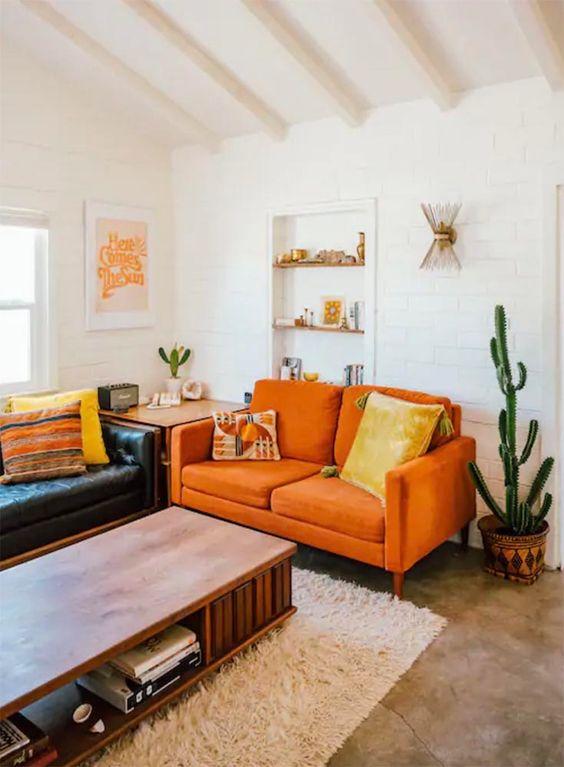 un soggiorno boho con un divano in pelle nera, un divanetto arancione, un tavolo basso e cactus in vaso è caldo e fresco